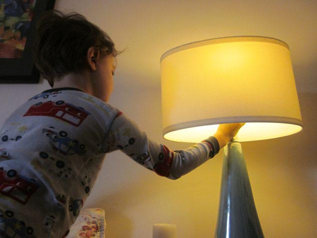 boy turning off light- eco tips for kids